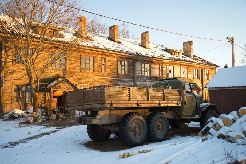 Stara sowieci ciężarówka ZIL-157 przy zaniechanym drewnianym domem w promieniach ustawia słońce Rosja fotografia stock