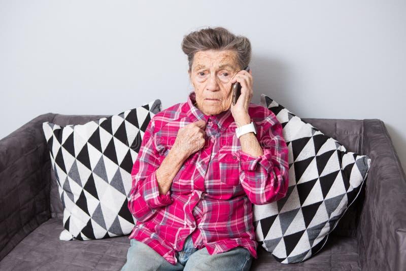 Stara starsza kobiety babcia z szarym włosy siedzi w domu na leżance używać ręka telefon, rozmowa telefoniczna obrazy stock