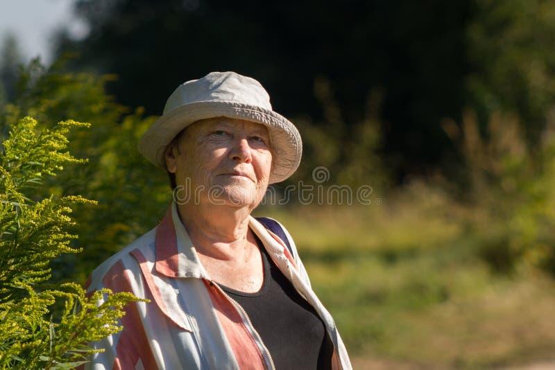 Stara starsza szczęśliwa kobieta ono uśmiecha się w ogródzie lub paek obraz royalty free