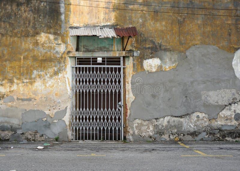 Stara starzejąca się ściana z starym falcowanie metalu drzwi obrazy stock