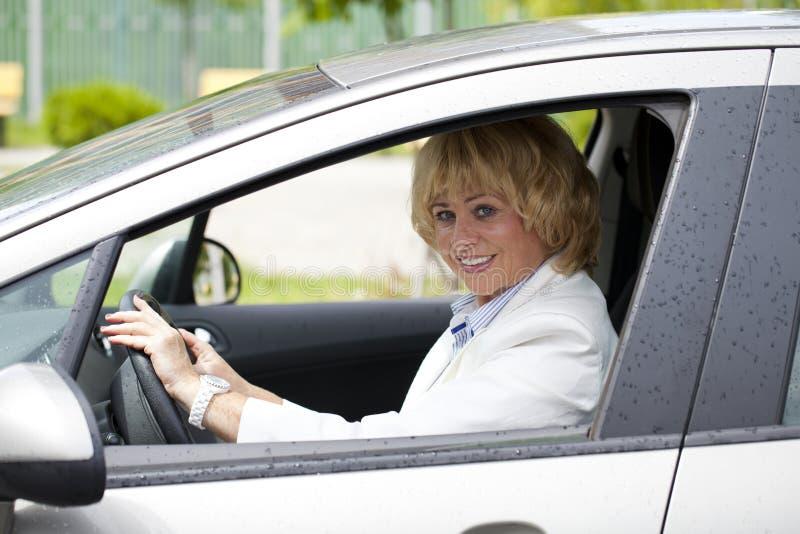 Stara szczęśliwa starsza kierowca kobieta 55-60 rok w kurtce Jedzie a.c. zdjęcie stock