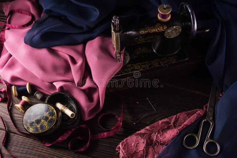 Stara szwalna maszyna, tkaniny, nożyce i inni akcesoria, zdjęcia royalty free