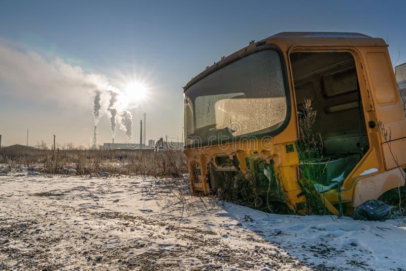 Stara taksówka, opuszczona na złomowisku na tle dnia z rur fabrycznych nudne i zdjęcie royalty free