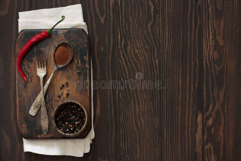 Stara tnąca deska, pieprze, rocznik łyżka na naturze i rozwidlenie, i zdjęcia stock
