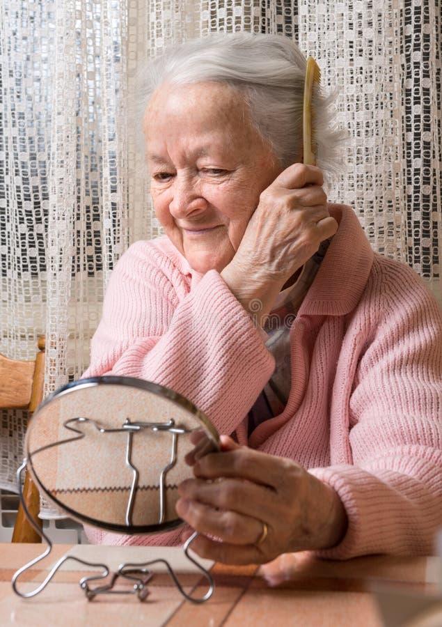 Stara uśmiechnięta kobieta czesze jej włosy fotografia royalty free