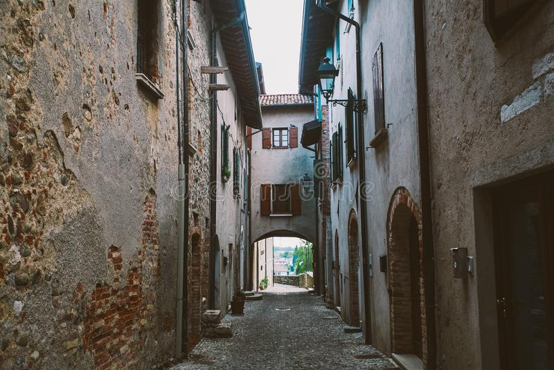 Stara wąska aleja w Tuscan wiosce - antykwarski włoski pas ruchu w Montalcino, Tuscany, Włochy fotografia stock