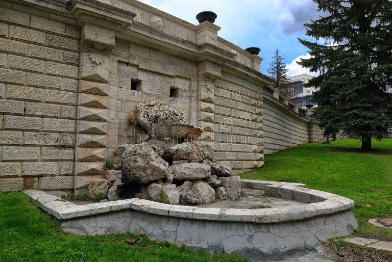 Stara zaniechana fontanna w kamiennej ścianie w parku zdjęcie royalty free