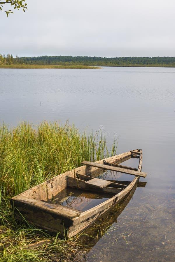 Stara zaniechana zalewająca drewniana łódź rybacka wiąże z arkaną drewniana karpa Drzewa odbijają w pluskoczącej powierzchni obraz royalty free