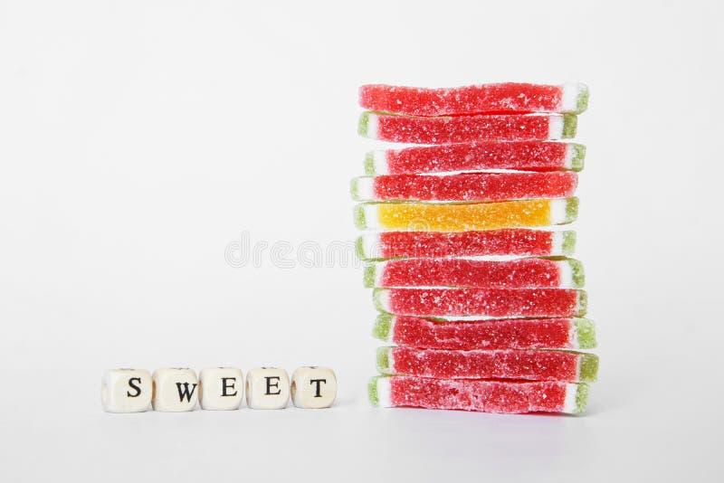 Staranna sterta słodcy marmoladowi kłamstwa na białej powierzchni Następny słowo komponujący listy: cukierki obrazy stock