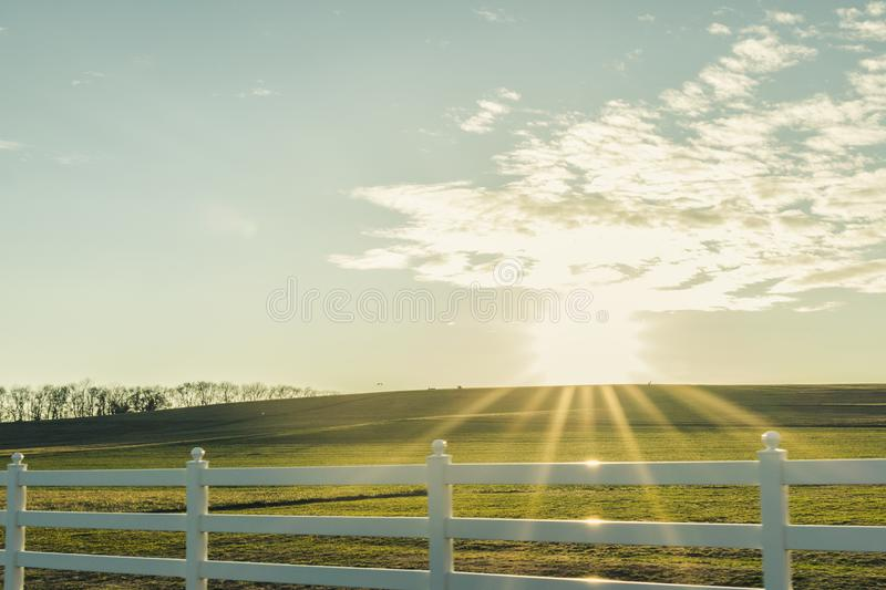 Starburst Sun over a Green Hill with a White Fence royalty free stock image