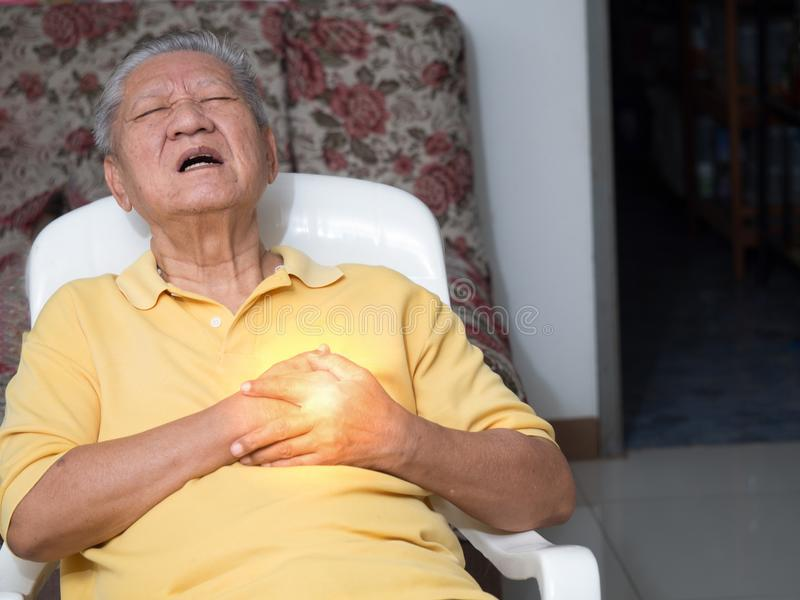 Starczy azjatykci mężczyzna siedzi na krześle przy żywym pokojem z atakami serca Oba starego człowieka ` s ręki na piersi przez c fotografia royalty free