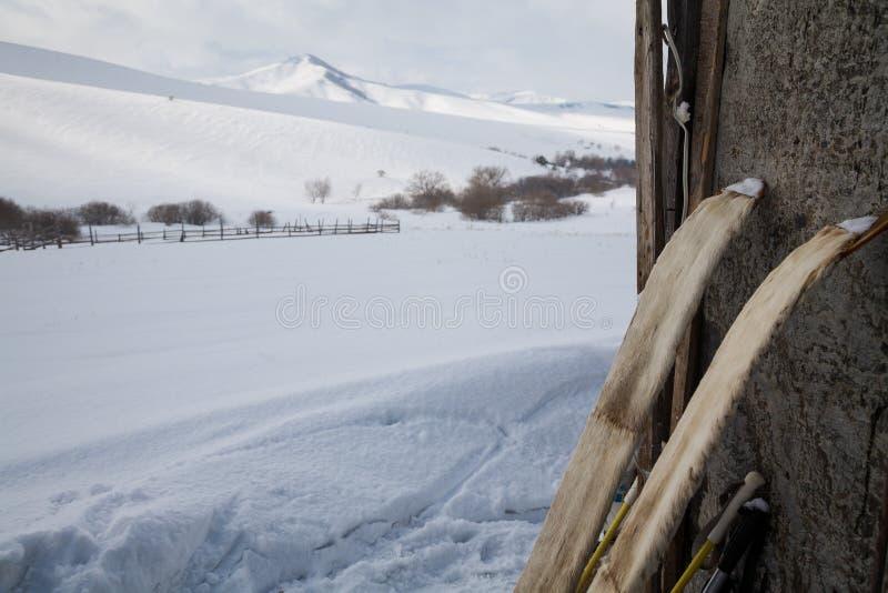 Stare łowieckie narty z futerkiem na śnieżnym tle obrazy royalty free