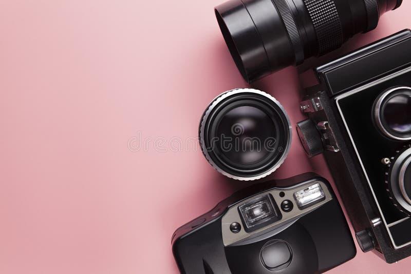 Stare analogowe kamery i obiektywy na różowią stół fotografia stock