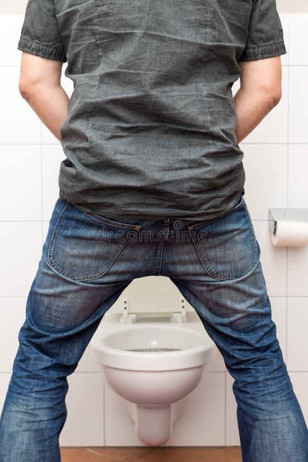 Stare d'orinata dell'uomo su nella toilette fotografia stock
