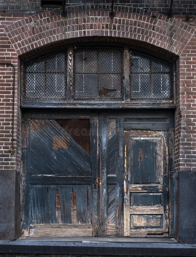 Stare drewniane drzwi na budynku fabryki cegieł z farbą obierającą obrazy royalty free