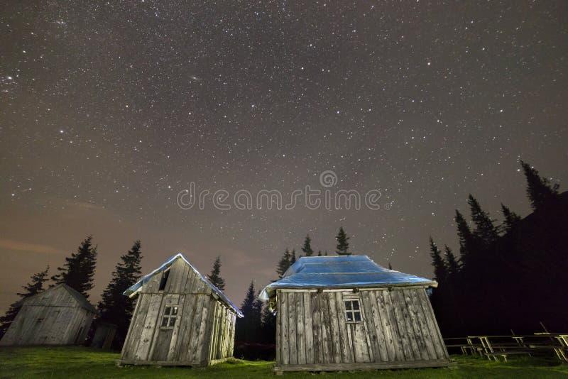 Stare drewniane pasterskie budy na górach rozjaśnia pod gwiaździstym niebem Szeroki kąt, kopii astronautyczny tło zdjęcia stock