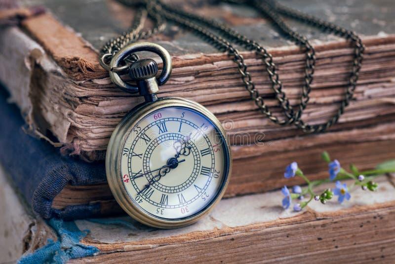 Stare książki i kieszeniowy zegarek zdjęcie royalty free
