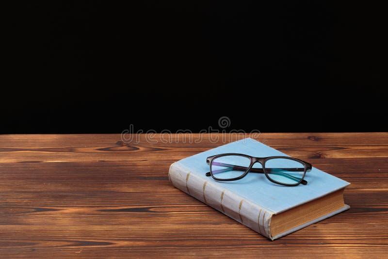 Stare książki i szkła na drewnianym tle obraz stock