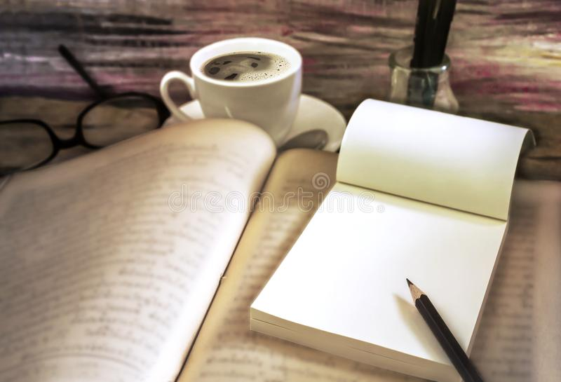 Stare książki z filiżanką, szkłami i ołówkiem na drewnianym stole, zdjęcia royalty free