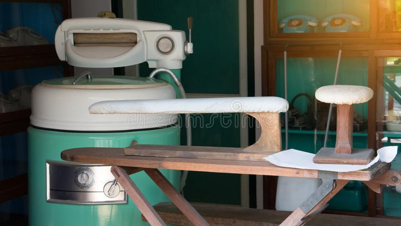 Stare rocznik pralki, elektryczna suszarki maszyna, pralniana prasowanie deska w pralni i suszą czyści biznesu sklep obrazy royalty free