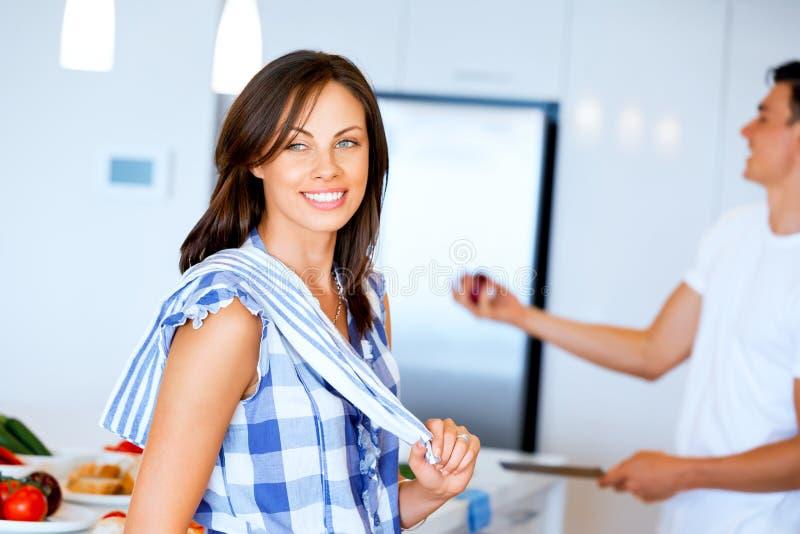 Stare sorridente della giovane donna con l'asciugamano di cucina fotografie stock libere da diritti