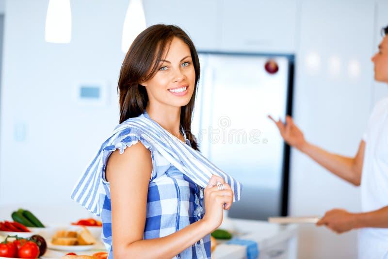 Stare sorridente della giovane donna con l'asciugamano di cucina fotografie stock