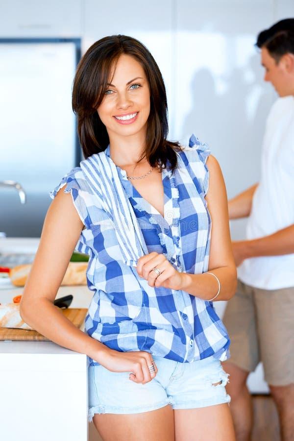 Stare sorridente della giovane donna con l'asciugamano di cucina immagini stock
