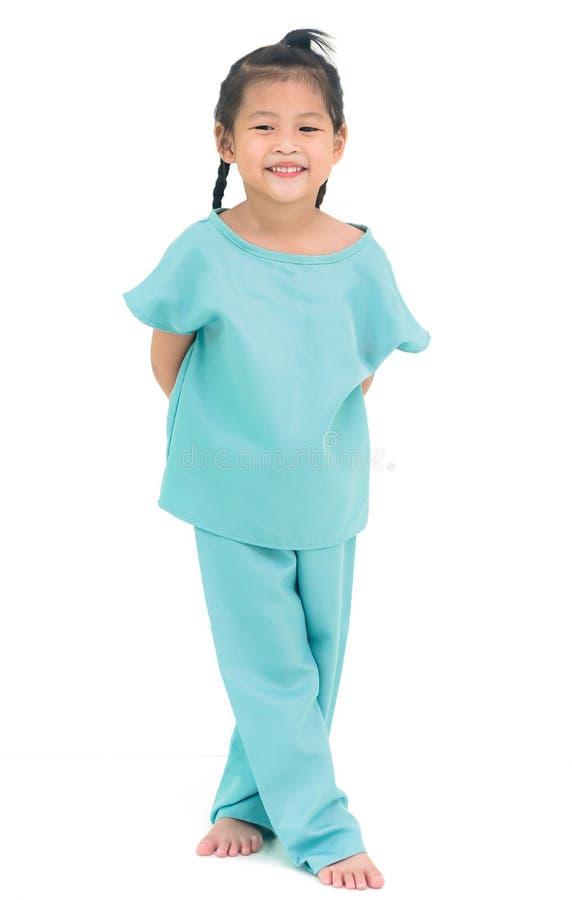 Stare sorridente della ragazza asiatica in vestito dall'ospedale, isolato su bianco fotografia stock libera da diritti