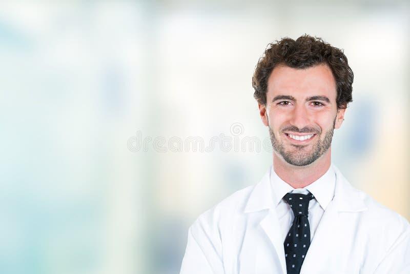 Stare sorridente di giovane medico maschio nel corridoio dell'ospedale fotografie stock