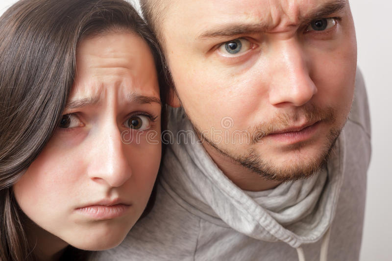 Stared at something. Doubt and wrinkle the forehead. Young couple with dubious looks forward, wrinkling his face in disbelief royalty free stock images