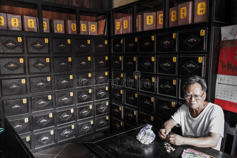Starego człowieka łasowania arachidy w starej aptece, Hoi, Quảng Nam prowincja, Wietnam zdjęcia royalty free