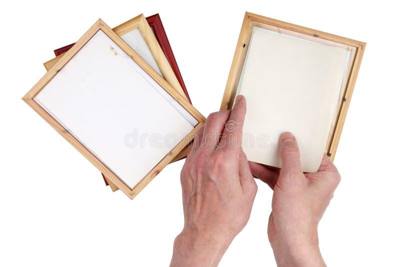 Starego człowieka dziad wkłada fotografie w drewniane fotografii ramy zdjęcia stock