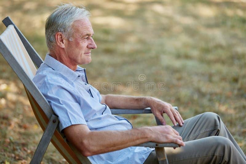 Starego człowieka obsiadanie relaksujący na pokładu krześle zdjęcie royalty free