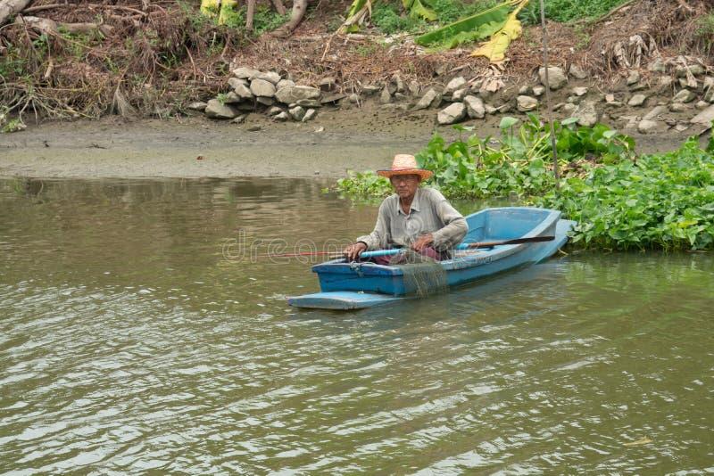 Starego człowieka połów na łodzi w rzece zdjęcia stock