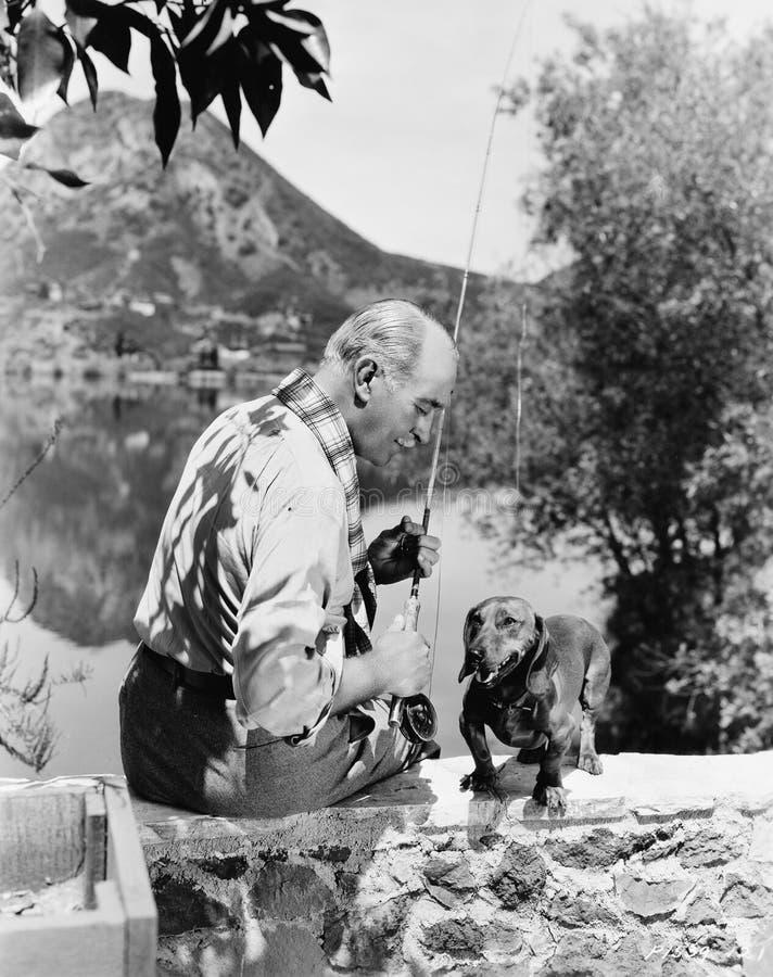 Starego człowieka połów z małym psem (Wszystkie persons przedstawiający no są długiego utrzymania i żadny nieruchomość istnieje D obrazy stock