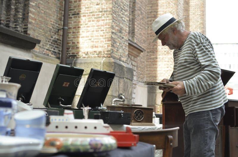 Starego człowieka sprzedawania antykwarski materiał w pchli targ fotografia stock