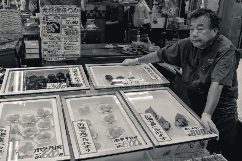 Starego człowieka sprzedawania owoce morza na Japońskim rybim rynku zdjęcia royalty free