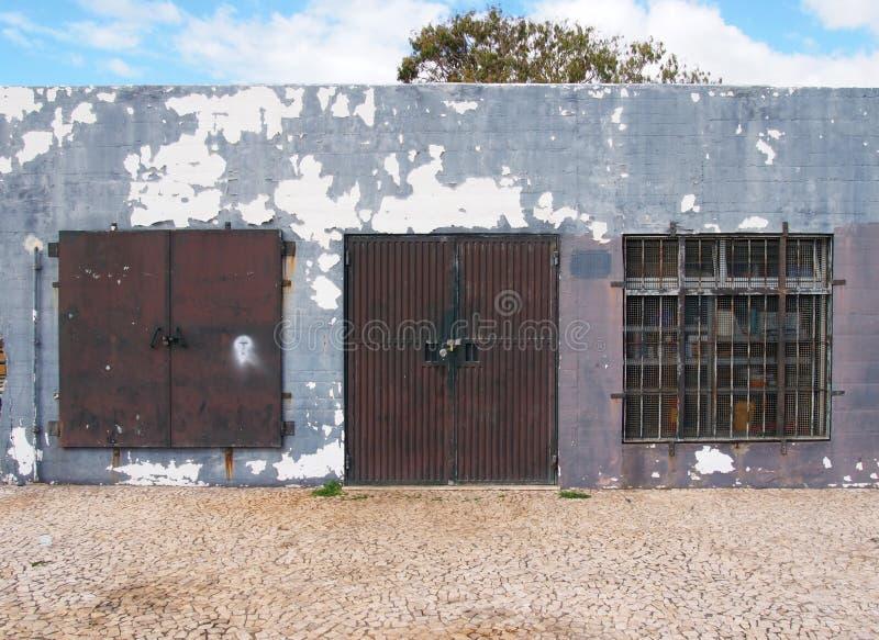 Starego depresja bieg puszka popielaty malujący składowy budynek z ośniedziałymi metali barami i zamkniętą metal ochroną zamyka k fotografia stock