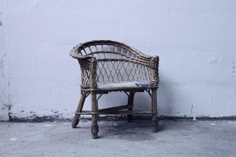 Starego krzesła osamotniony odpoczywać przed betonową ścianą obrazy stock
