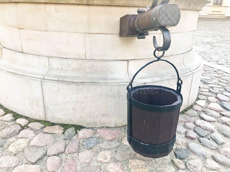 Starego małego rocznika antykwarski wiadro deski dla dobrze brukował drogę przeciw tłu amenia zdjęcie royalty free