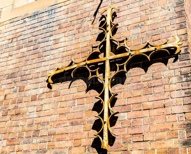 Starego metalu projekta chrześcijanina antykwarski krzyż dołączał na czerwonym ściana z cegieł obraz royalty free