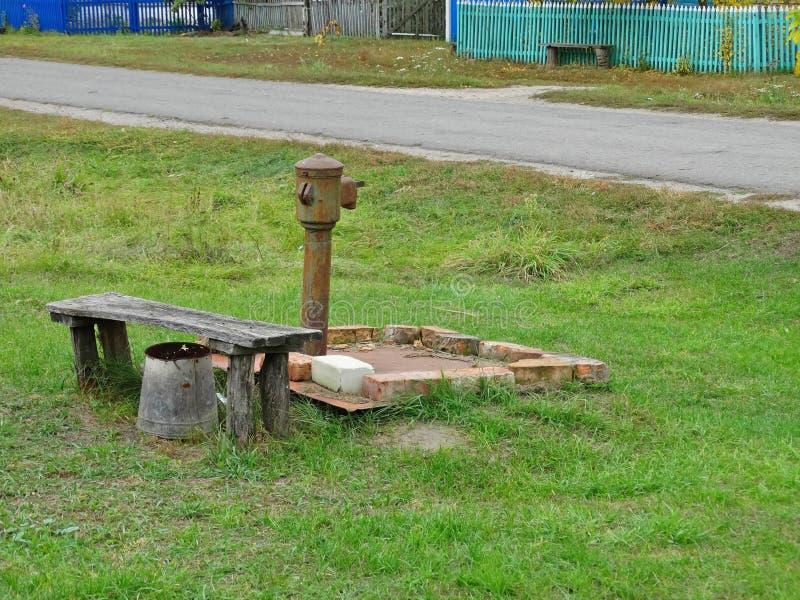 Starego ośniedziałego żelaza well i drewniana ławka wśród zielonej trawy zdjęcie stock