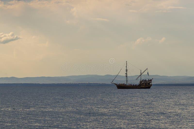 Starego pirata drewniany statek żegluje w wodzie przeciw tłu zmierzch fotografia royalty free