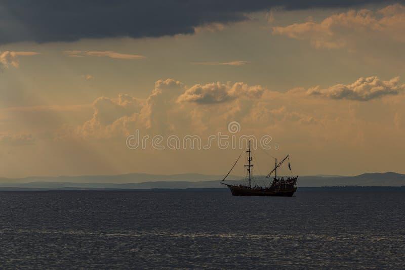 Starego pirata drewniany statek żegluje w wodzie przeciw tłu zmierzch zdjęcia royalty free