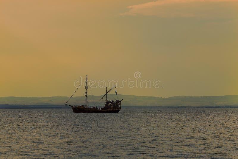 Starego pirata drewniany statek żegluje w wodzie przeciw tłu zmierzch zdjęcie royalty free