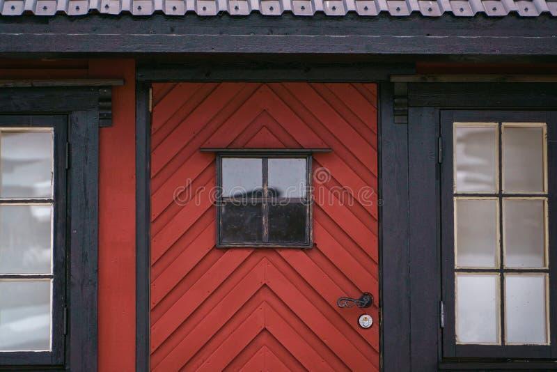 Starego rocznika drewniany dzwi wejściowy z okno na czerwonym domu na wsi Fasadowa powierzchowność, zbliżenie widok Retro wieś zdjęcia royalty free