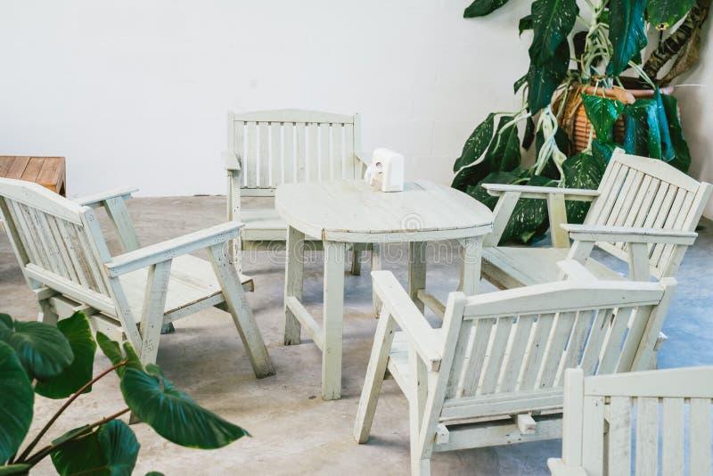 Starego rocznika drewniany krzesło z drzewa i rośliny inside pokojem obrazy stock