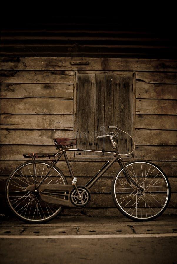 Starego stylowego brąz rowerowy i drewniany drzwi zdjęcie royalty free