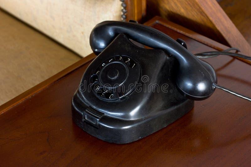 Starego talerzowego rocznika zakurzony czarny telefon na biurku zdjęcia stock