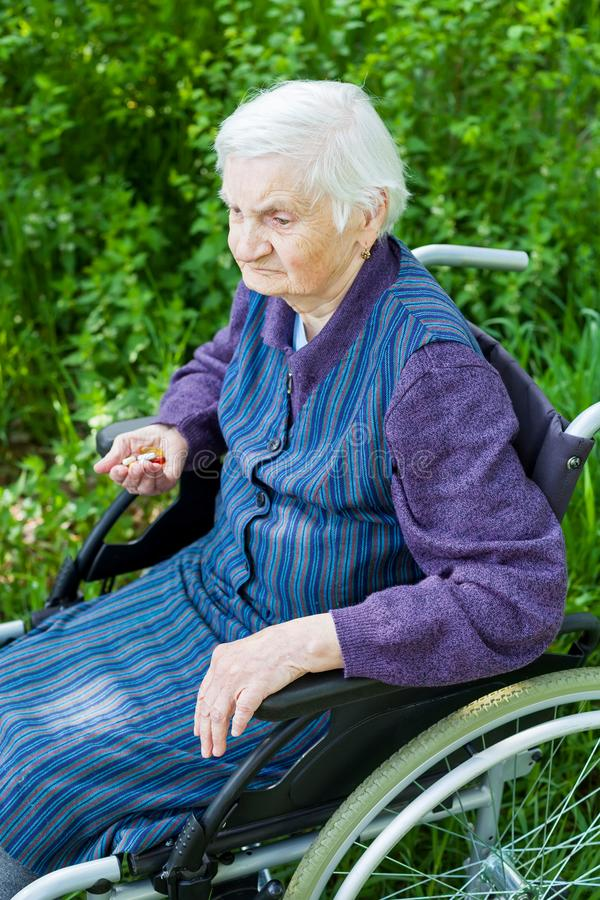 Starej damy obsiadanie w wózku inwalidzkim fotografia stock